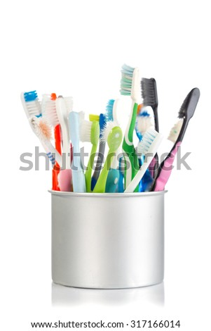 Group of old and used toothbrush in metal cup , isolate on white background
