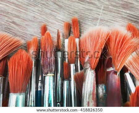 Group of old paint blushes on wooden in orange tone - stock photo