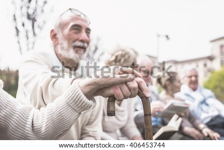 Group of old people making activities outdoor. Couple hands on a cane as main concept - stock photo