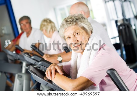 Group of older mature people exercising in the gym - stock photo