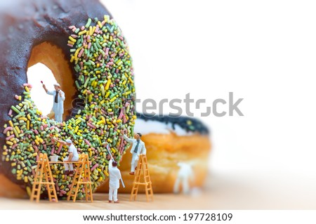 Group of painters painting over huge donut. Macro photo