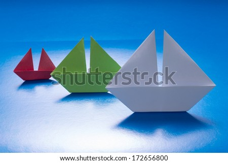 Group of Paper Ships Sailing on Blue paper sea. Origami Boat. Paper Sea - stock photo