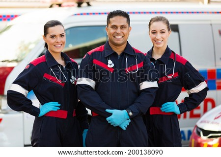 group of paramedics standing in front of an ambulance - stock photo