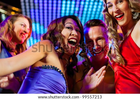 Group of party people - a man and women - dancing in a disco club to the music