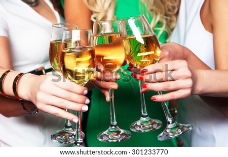 Group of partying girls clinking flutes with sparkling wine, close up - stock photo