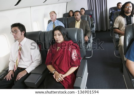 Group of passengers on airplane - stock photo
