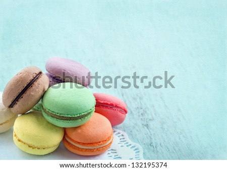 Group of pastel color macaroons on blue textured shabby chic background, with room for copy space - stock photo