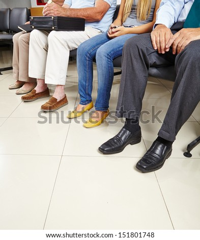 Group of patients sitting in waiting room of a doctor - stock photo