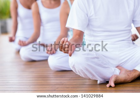 Group of peaceful people meditating  in a yoga studio - stock photo