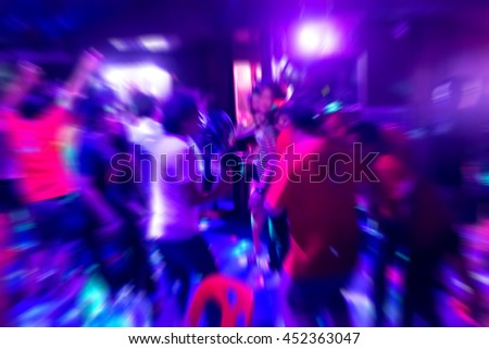Group of people are dancing under purple light in the club feeling fun and happy
