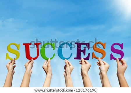 Group of people are holding word Success under blue sky - stock photo