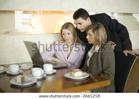 Group of People at the Cofe Table with Laptop. Short Depth of Focus (On Woman's in Pink Jacket Face). - stock photo
