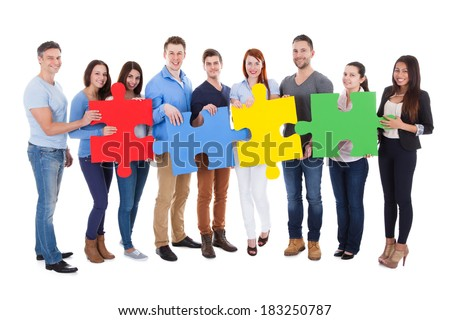 Group of people connecting puzzle pieces over white background
