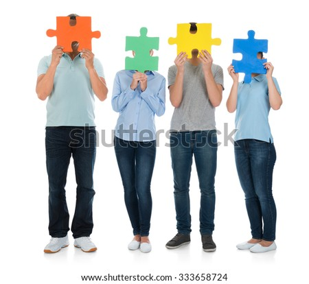 Group Of People Covering Face With Puzzle Pieces Over White Background - stock photo