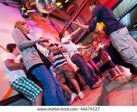 Group of people dancing in a trendy nightclub - stock photo