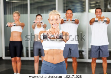 group of people doing aerobics with dumbbells in gym - stock photo