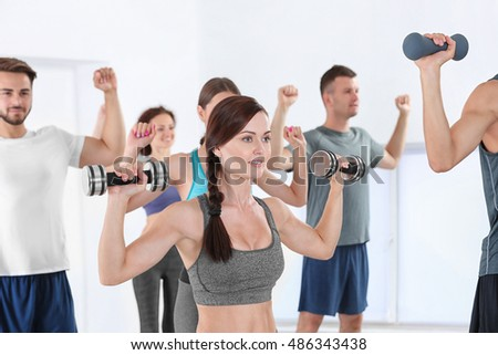 Group of people doing exercises with dumbbells in gym