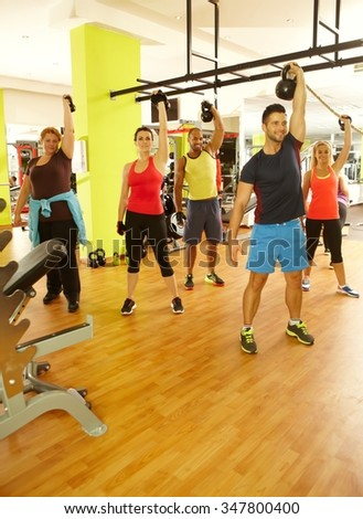 Group of people doing fitness workout in gym with dumbbells. - stock photo