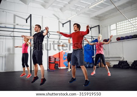 Group of people doing jumping jacks at gym - stock photo