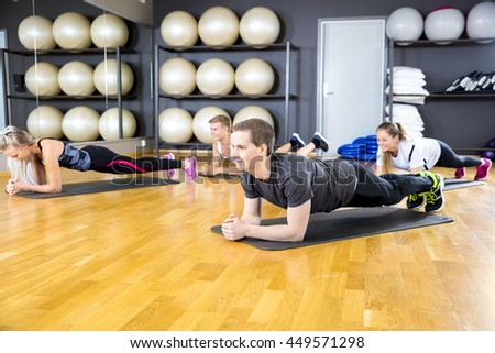 Group of people doing plank at the fitness gym class - stock photo