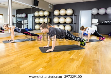 Group of people doing pushups at the fitness gym class - stock photo