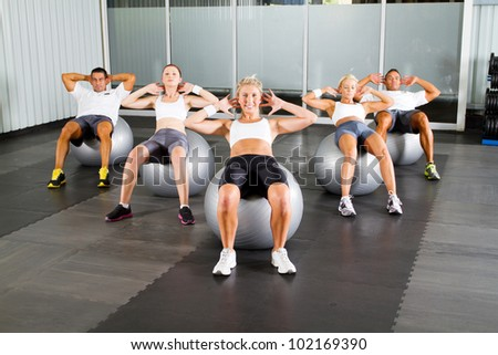 group of people doing workout with fitness balls in gym - stock photo