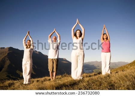 Group of people doing yoga on the mountains. - stock photo