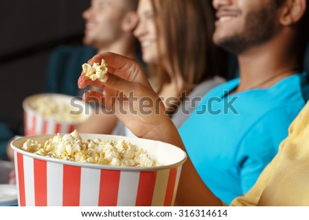 Group of people eating popcorn in the cinema - stock photo