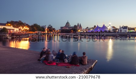 "Group of people enjoy the evening during Galway Art Festival with ""Big Top"" and Cathedral on the bank of Corrib river in Galway, Ireland"