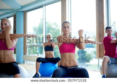 group of people exercise with balls on yoga class in fitness gym - stock photo