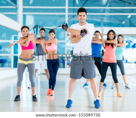Group of people exercising at the gym looking happy  - stock photo