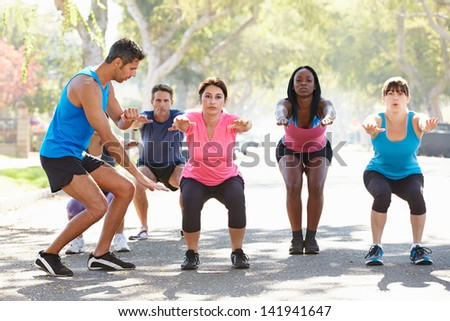 Group Of People Exercising Street With Personal Trainer