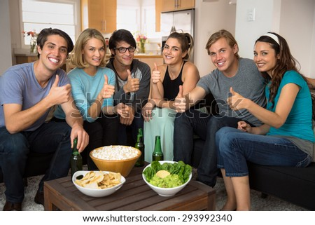 Group of people give thumbs up celebrating at home happy together as friends - stock photo