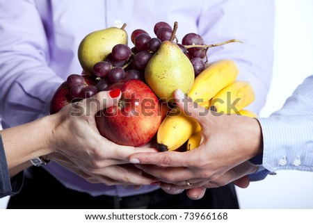 Group of people hands holding apples, oranges, pears, grapes and bananas (selective focus) - stock photo