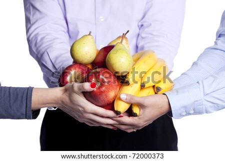 Group of people hands holding apples, oranges, plums and bananas (selective focus) - stock photo