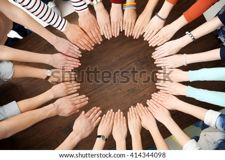 Group of people hands together on wooden background - stock photo