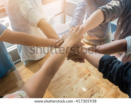 Group of people hands together on wooden background in office - stock photo