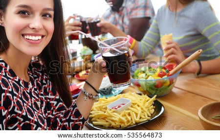 Group of people having dinner together while sitting at wooden table