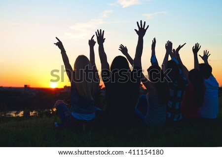 Group of people having fun outdoors; sunset