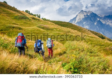 group of people hiking through a scenic mountain view