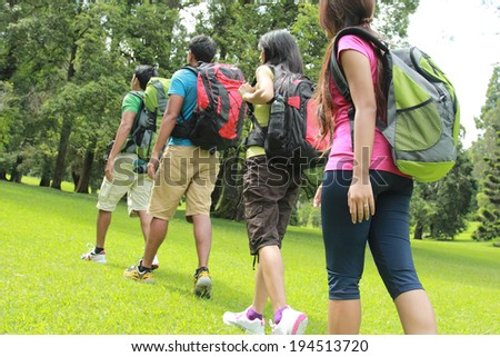 group of people hiking together. walking on the grass - stock photo