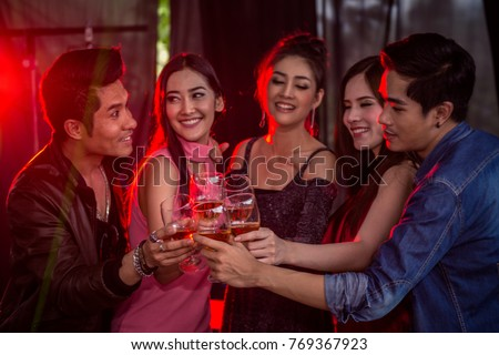 Group of people holding glasses of alcohol drinks making a toast together at night club, party celebration concept.