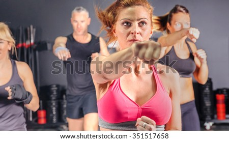 Group of people in a hard boxing class on gym training punch - stock photo