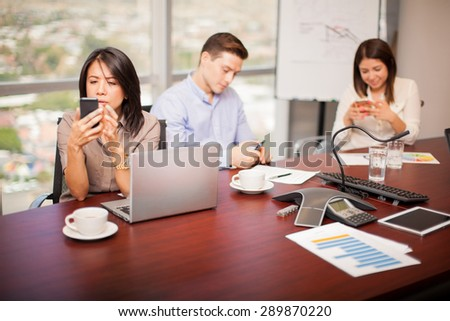 Group of people in a meeting room using their smartphones and ignoring work for a while - stock photo