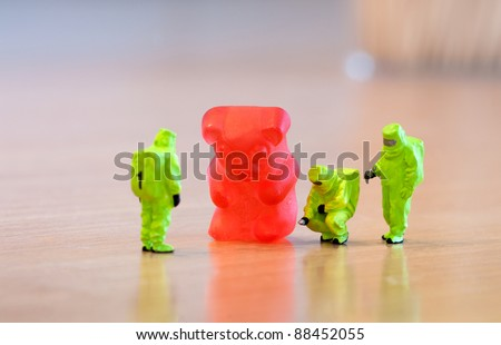 Group of people in protective suit inspecting a jelly bear. Unhealthy food concept - stock photo