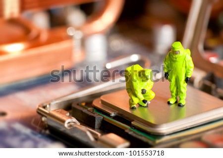 Group of people in protective suit inspecting computer processor - stock photo