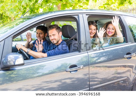 Group of people in the car. They are a multicultural group of friends leaving for a trip. There are two men sitting on the front and two women on the back. They are smiling and waving their hands.