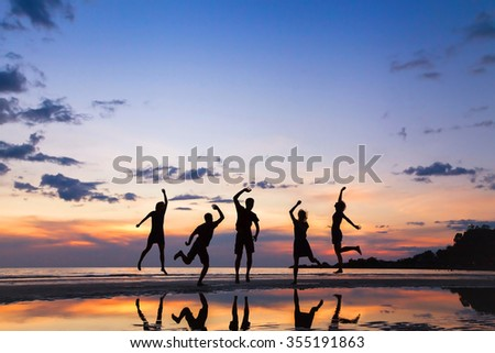 group of people jumping on the beach at sunset, silhouette of friends having fun together