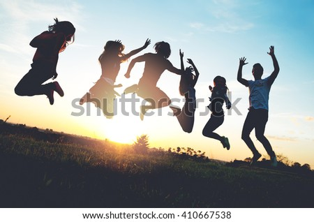 Group of people jumping outdoors; sunset  - stock photo
