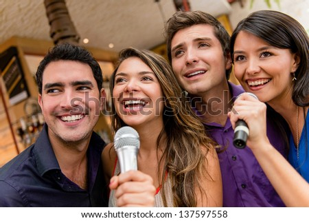 Group of people karaoke singing at the bar having fun - stock photo